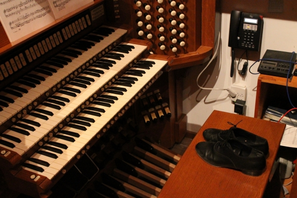 Organ console with organ shoes on the bench. Photo by Harry Gould.
